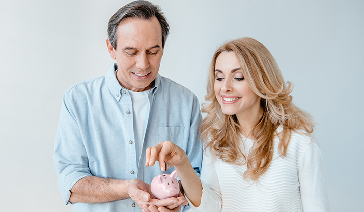 a happy couple budgeting and inserting a coin in their piggybank because they knew how to talk about money together